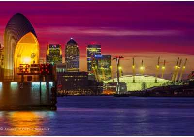 The Thames Barrier with Canary Wharf and O2 Arena at sunset